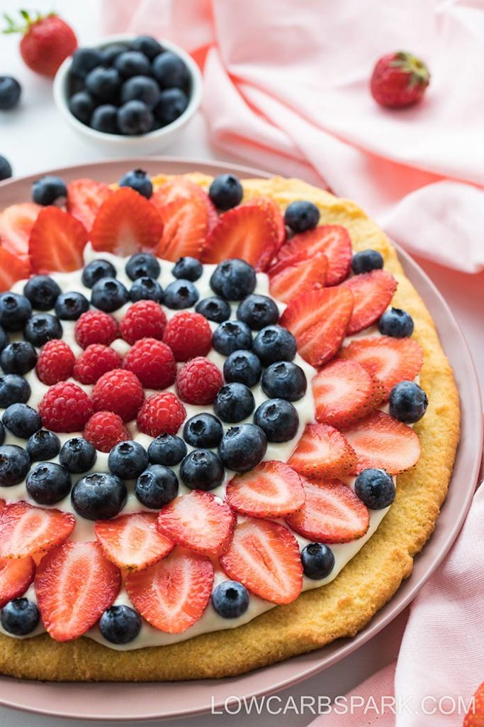 best keto fruit pizza decorated with berries and cream cheese frosting