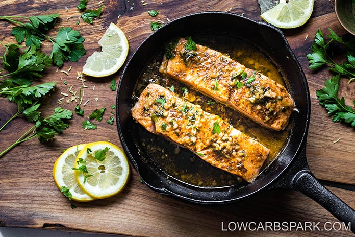 Roasted Salmon on a black skillet placed on a wood surface